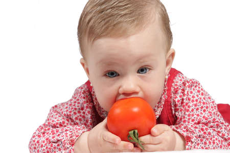 Portrait of a girl with red dress and  a tomato in the hands photo