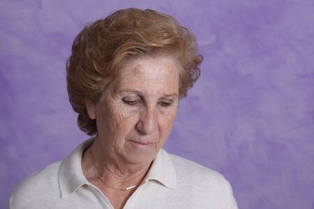 Portrait of a elderly woman with serene look on a purple background photo