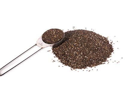 measuring spoon: chia seeds in metal measuring spoon on white