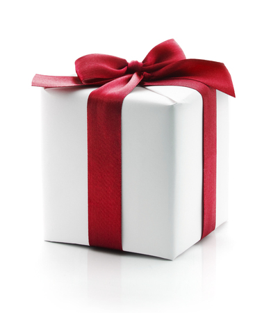 Gift box present. Wrapped with red ribbon and bow and isolated over a white background. Archivio Fotografico