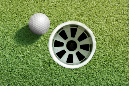 Hole in one golf ball on a putting green.