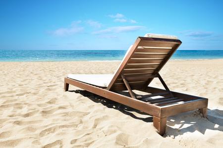 Deckchair on a sunny tropical beach. Holiday destination for the summer.