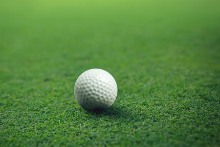 Golf ball on green grass ready for putting.