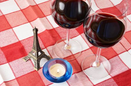 Souvenir Eiffel tower, candle and a pair of wineglasses on the table photo