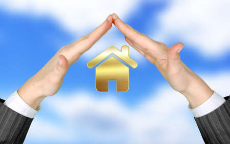 Hands of real estate agent protect home Stock Photo