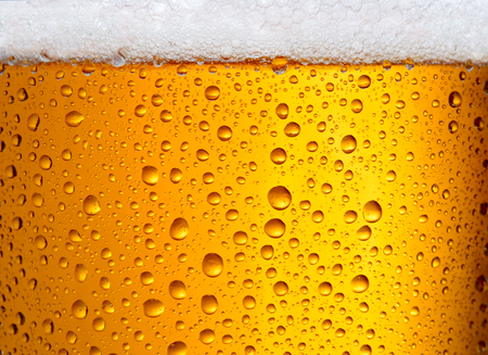 close-up view of glass with beer with droplets as textured background Banco de Imagens