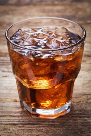 single glass of cola with lot of crashed ice on wooden background