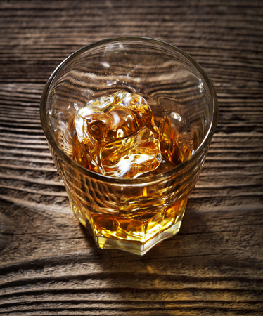 single glass of alcohol drink whiskey with ice on wooden background