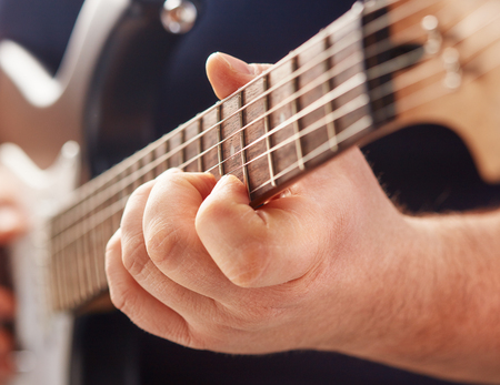 close-up of male hands playing electric guitar