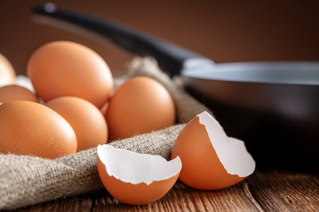 pile of chicken eggs with pan on wooden table