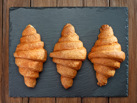 fresh baked croissants on slate on wooden table