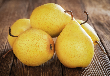 pile of ripe yellow pears on wooden background