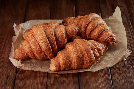 fresh baked croissants in paper on wooden table