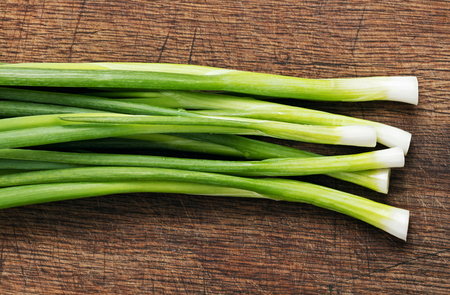 heap of green onion on wooden background Imagens
