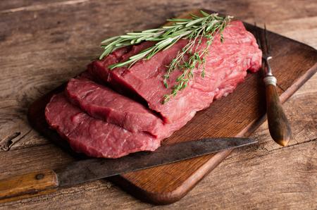 Gran trozo de carne de vacuno cruda en la mesa de madera