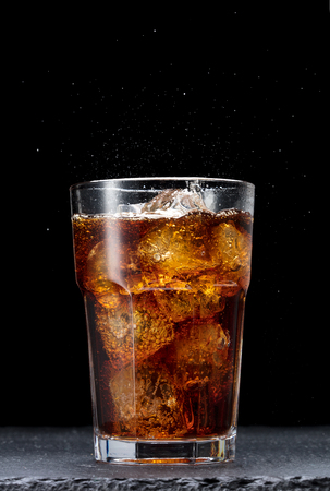 single glass of cola with ice cubes on black background