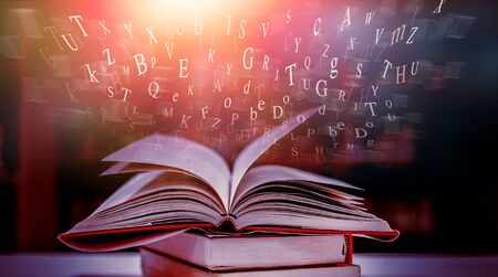 Imagine opening an old book blurred with magic power on the table and the English alphabet floating above the book with magic light as a beautiful background design. Imagens