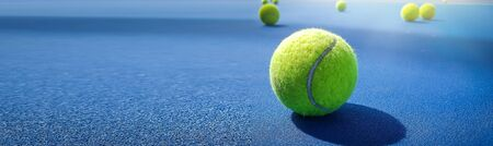Close-up shots of green tennis balls on a blue field with beautiful background shadows