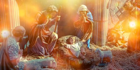 Traditional Christmas scenes and sacred light shining for use in illustration design Nativity scenes with Jesus baby on the manger with carvings, including Jesus, Mary, Joseph, sheep and magi Stock Photo