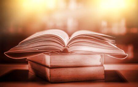 Pila di libri in biblioteca e sfocatura dello sfondo dello scaffale