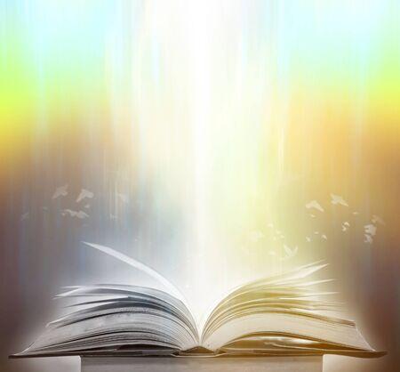 Il libro sfocato che è stregato dalla magia, la luce magica nell'oscurità, con la luce brillante che risplende come il potere di cercare la conoscenza. Per la ricerca e l'uso come sfondo sfocato Archivio Fotografico