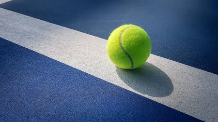Close-up shots of tennis balls in tennis courts With a mesh as a blurred background And the light shining on the ground makes the image beautiful