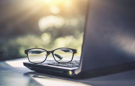 Okulary umieszczone na laptopie w bibliotece.