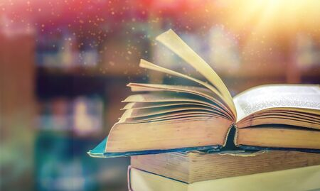 The blurred book that is bewitched with magic, the magic light in the dark, with the bright light shining down as the power to search for knowledge. For research and use as a blurred background Stock Photo