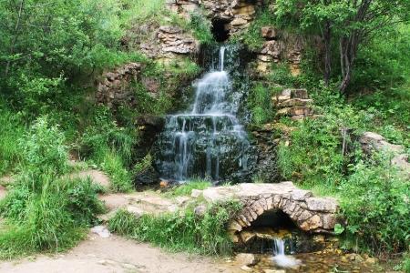 green vegetation: Small summer waterfall with green vegetation around