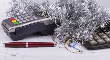 Business Christmas - payment terminal, calculator, pen, tinsel, eyeglasses photo