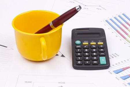 cup and saucer: Business still life of pen in cup, saucer, calculator
