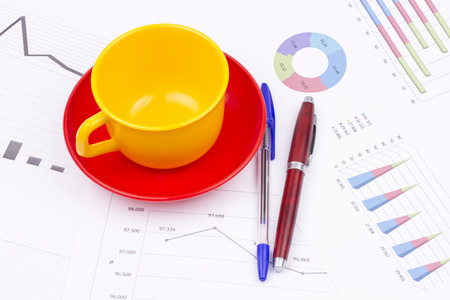 cup and saucer: Business still life of pens, cup, saucer