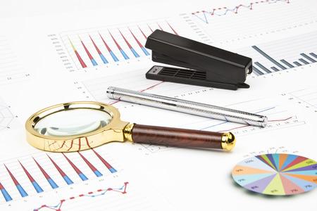 charts graphs: Business still-life of a charts, graphs, pen, magnifier, stapler