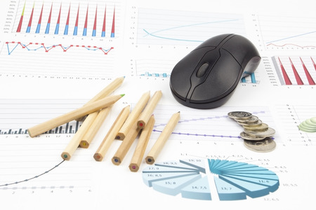Business still-life of pencil, charts, coins, computer mouse Stock Photo