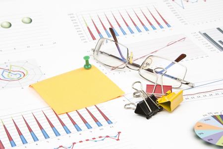 Business still-life of sticker, graphs, eyeglasses, pushpin, paperclip Stock Photo