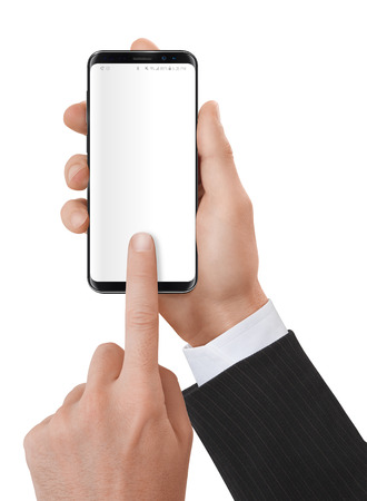 Elegant dressed man holding a smartphone in his hands with neutral white screen. Banco de Imagens