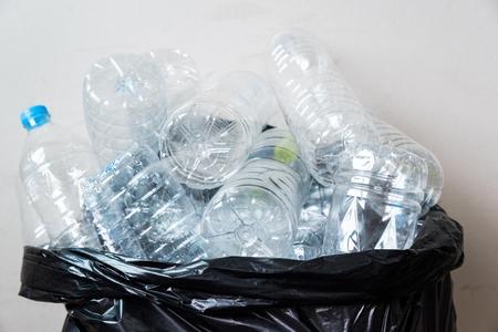 リサイクルするために取られるのを待っている黒ごみ袋のプラスチックボトル。