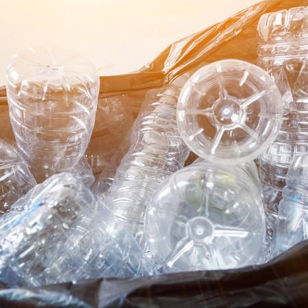 黒いゴミ袋の中のペットボトルは、リサイクルのために取られるのを待っています。 写真素材