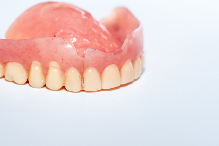 Old denture on a white background.