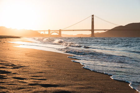 Sunset on a golden beach in San Francisco with the Golden Gate