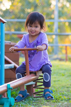 Happy little girl is riding on see-saw on playground photo