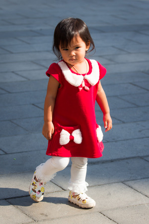 Cute little girl is walking on the ground photo