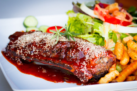 BBQ Ribs - Marinated pork ribs with salad, french fries and barbeque sauce. photo