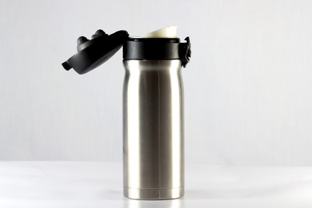 insulated drink container: Stainless vacuum bottle cap open on white background Stock Photo