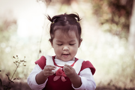 Cute little girl with look at small flower on her hand on meadow background in retro style photo