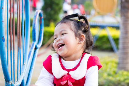 Cute little girl is playing slide on playground photo