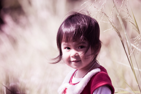 Cute little girl is smiling on meadow in retro style photo