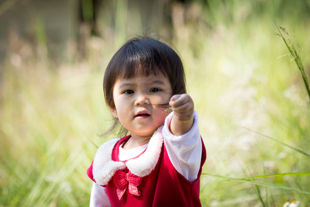 Cute little girl on stretch out her hand to give small flower on meadow background photo