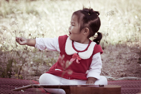 Cute little girl with ukulele look at small flower on her hand on meadow background in retro style photo