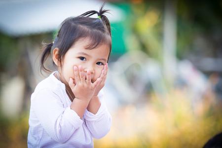 Wordt schattige kleine holding haar gezicht en glimlach